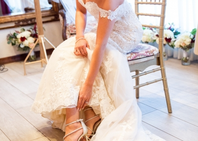 bride to be adjusting shoes in bridal suite