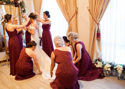 bridesmaids dressing the bride