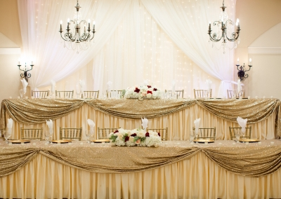 head table dressed in white and gold