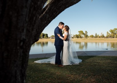 Villa Tuscana Reception Hall in mesa showing nearby park area showing bride and groom under tree by lake